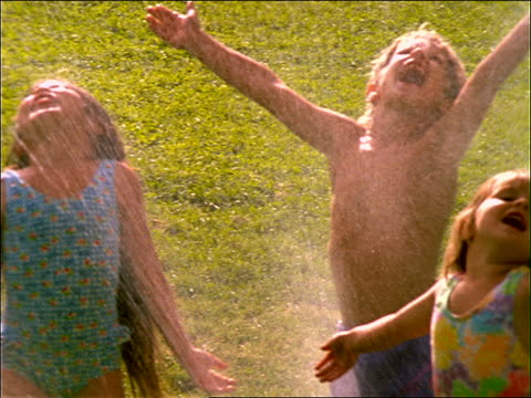 slow motion 2 girls and boy playing in sprinkler in grass