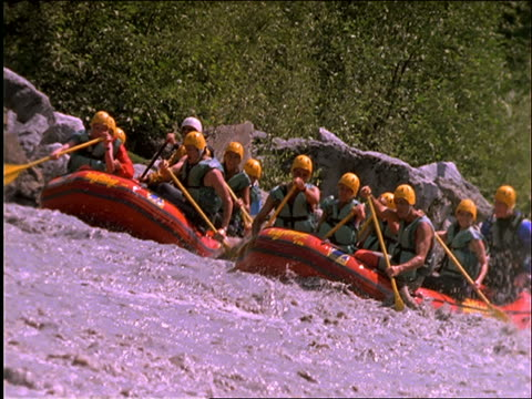 slow motion 2 groups of people white water rafting in rapids