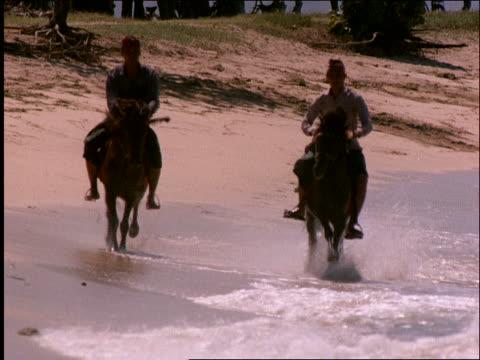 slow motion 2 men riding horses in surf on beach toward camera / Nusa Sua Beach/ Bali / Indonesia