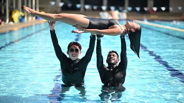 slow motion 2 men throwing female swimming into water splashing in swimming pool - ecstatic stock videos & royalty-free footage