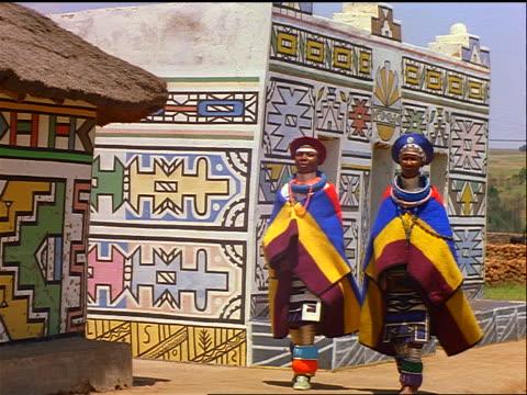 slow motion 2 n'debele tribal women in native dress walking past huts with colorful designs / africa - 民族衣装点の映像素材/bロール