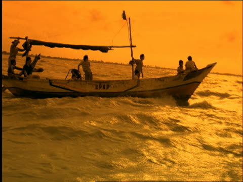 slow motion 2 small boats on rough ocean / Indramayu / West Java / Indonesia / orange filter