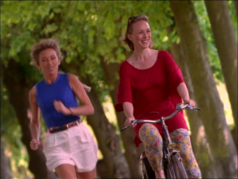 slow motion 2 women jogging + riding bicycle toward camera / Paris