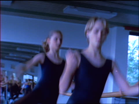 blue slow motion 2 young blonde girls in ballet class practicing at barre / turn away from camera - barre stock videos & royalty-free footage