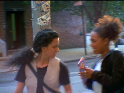 slow motion 2 young women (1 black, 1 iranian) stopping on street corner looking at maps + pointing - 1990~1999年点の映像素材/bロール
