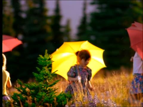 vidéos et rushes de slow motion 3 girls with umbrellas skipping thru field - seulement des petites filles
