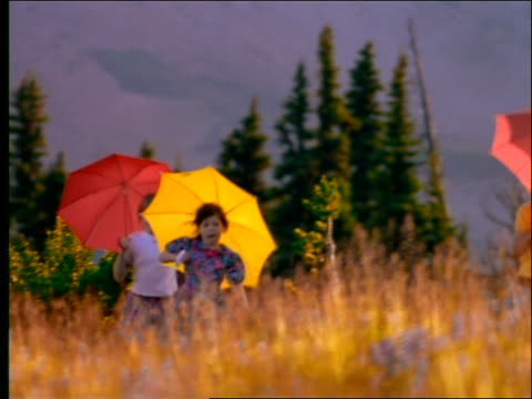 slow motion 3 girls with umbrellas skipping thru field - skipping along stock videos & royalty-free footage