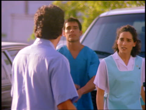 vidéos et rushes de slow motion 3 hospital workers (1 female) talking + hurrying towards camera outdoors - parking