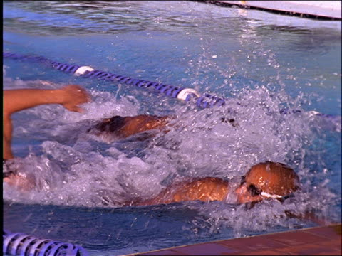 slow motion 3 male swimmers reach finish line / 1 raises arms - freibad stock-videos und b-roll-filmmaterial