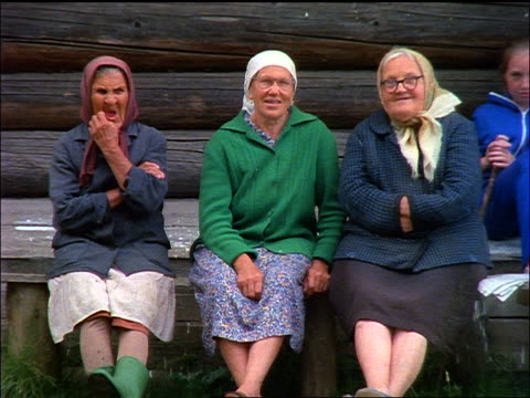 slow motion 3 senior russian women wearing babushkas sitting + looking at camera - 東ヨーロッパ民族点の映像素材/bロール