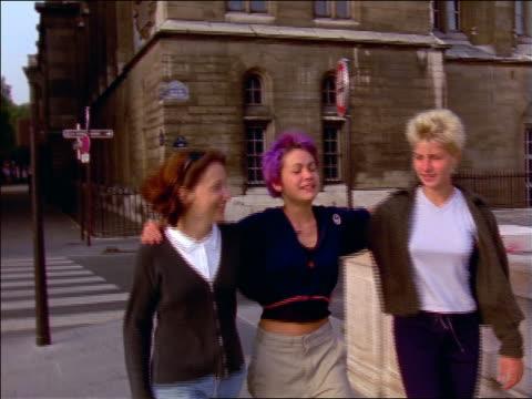 slow motion 3 teenage girls (1 punk) walking on street + greeting teenage boy / Paris, France
