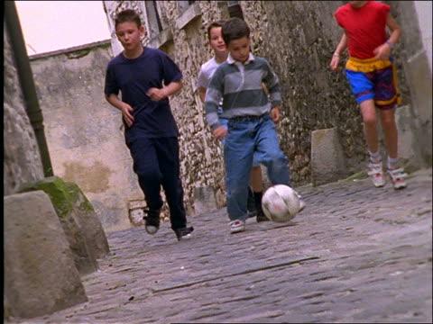 vidéos et rushes de slow motion 4 boys kicking soccer ball in street / paris - petits garçons