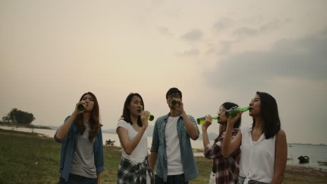 vidéos et rushes de ralenti 4k, cheering une bouteille de bière groupe d'amis chantant et buvant de la bière dans un voyage de camping - activités de week end