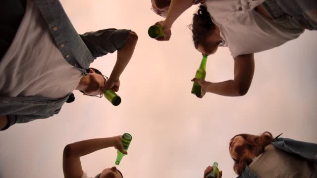 zeitlupe 4k, cheering eine bierflasche gruppe von freunden singen und trinken bier in einem camping-ausflug - jugendkultur stock-videos und b-roll-filmmaterial