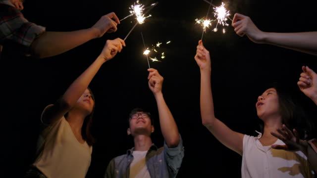 vidéos et rushes de ralenti 4k, groupe d'amis chantant et jouez des feux d'artifice dans un voyage de camping - refreshment