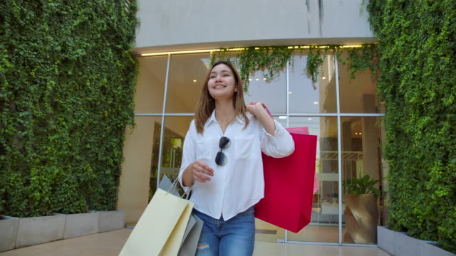 slow motion 4k the beautiful woman carrying shopping bags in various colors and she smiled happily. that has bought things she likes, and it is a clear day. - shopping bag stock videos & royalty-free footage