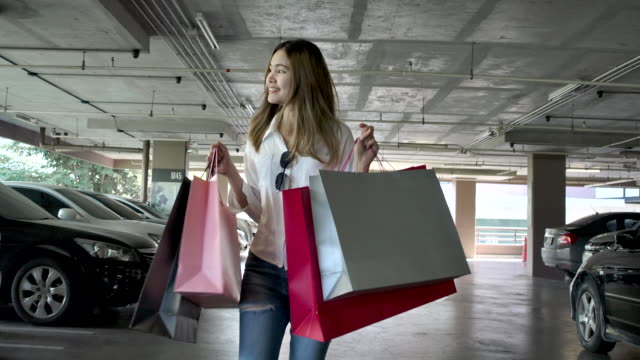 slow motion 4k the beautiful woman carrying shopping bags in various colors and she smiled happily. that has bought things she likes, and it is a clear day. - car park stock videos & royalty-free footage