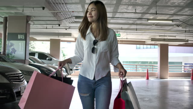 slow motion 4k the beautiful woman carrying shopping bags in various colors and she smiled happily. that has bought things she likes, and it is a clear day. - parking stock videos & royalty-free footage