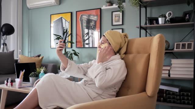 vídeos y material grabado en eventos de stock de video 4k a cámara lenta de mujer hablando con un amigo a través de una llamada de voz durante el tratamiento de belleza en casa - personas bellas