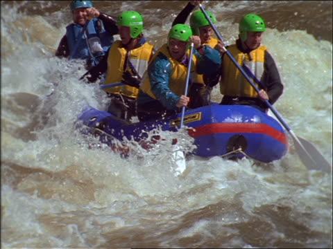 slow motion 5 men river rafting in rapids