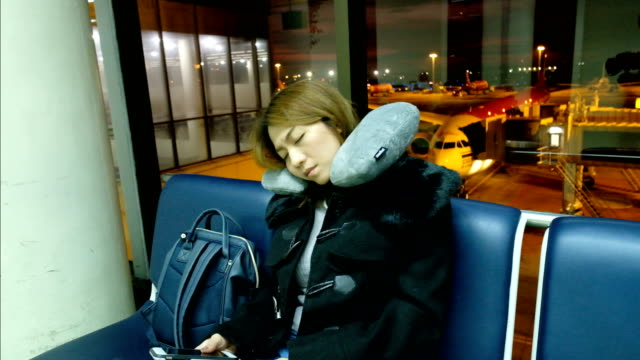 vídeos de stock e filmes b-roll de 4k slow motion: a asian woman fell asleep on chair at international airport terminal. passengers of transfer flight waiting for boarding - aviation fatigue