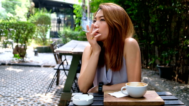 vídeos de stock e filmes b-roll de 4k slow motion : a asian woman smoking cigarette in coffee cafe just for relaxation. - estilo de vida pouco saudável