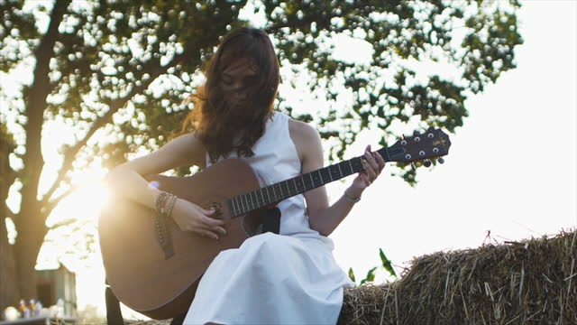slow motion a beautiful young asian woman in white dress is playing guitar on a haystack in the morning sunlight lens flare. - white dress stock videos & royalty-free footage
