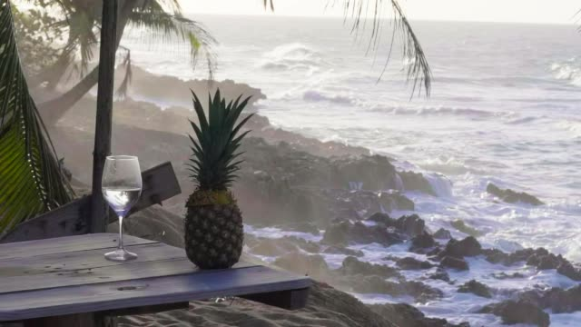 slow motion: a cocktail and a pineapple sit near the shore - tropical cocktail stock videos & royalty-free footage