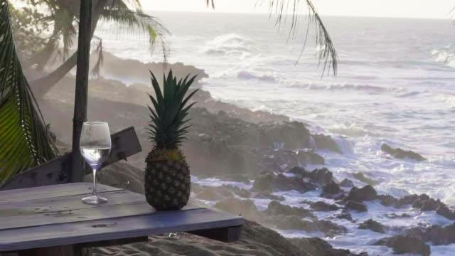 vídeos y material grabado en eventos de stock de slow motion: a cocktail and a pineapple sit near the shore - hispaniola
