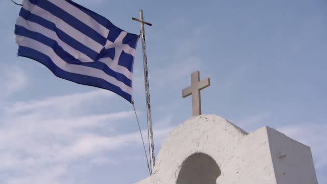 slow motion: a frayed greek flag flies atop a church bell tower - frayed stock videos & royalty-free footage