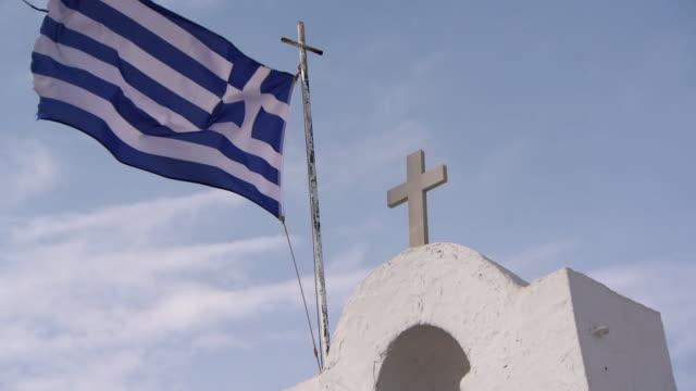 slow motion: a frayed greek flag flies atop a church bell tower - ausgefranst stock-videos und b-roll-filmmaterial
