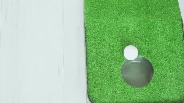langsame bewegung: ein golfball rollt in ein loch - minigolf stock-videos und b-roll-filmmaterial