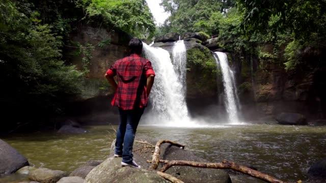 vidéos et rushes de ralenti, un homme restant devant une chute d'eau dans les montagnes - chapeau de paille