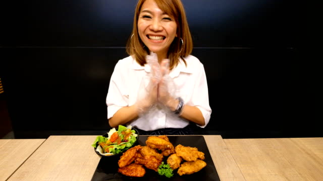 4K Slow motion : A woman is excited and glad to eat fried chicken like she has never eaten before.