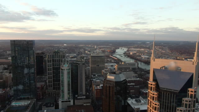 slow motion aerial back: financial district in nashville by cumberland river nearing dusk - approaching stock videos & royalty-free footage