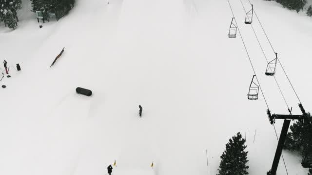 スローモーション、フルウィンターギアのスノーボーダーの空中ドローンショットは、雪の日にコロラド州ボルダー近くのエルドラスキーリゾートで森とスキーリフトを背景にジャンプで「� - winter点の映像素材/bロール