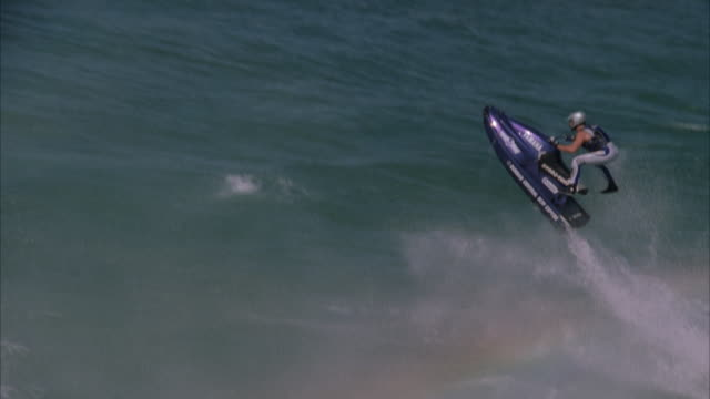 slow motion aerial shot of a jetskier performing a trick in the air as he ramps a wave - acquascooter video stock e b–roll