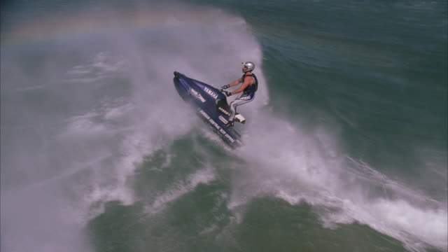 Slow motion aerial shot of a jetskier performing a trick in the air as he ramps a wave