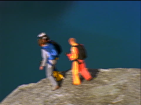 slow motion AERIAL three male base jumpers jumping from + falling past cliff / Sweden