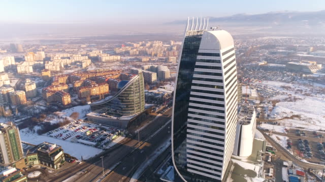 Slow motion aerial view drone rotating around corporate office building tower