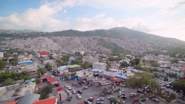 slow motion aerial view of carrefour town in haiti with mountains behind - haiti stock videos & royalty-free footage