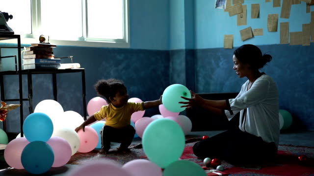 slow motion african kid giving balloon to african woman in orphanage - poor family stock videos & royalty-free footage