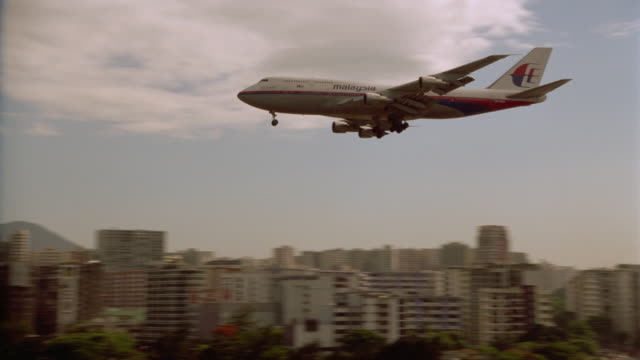 slow motion airliner landing on runway with skyline in background / Hong Kong