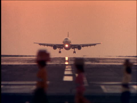 slow motion airliner landing / women with baskets on heads in foreground / balinese women carry temple offerings - - landing touching down stock videos & royalty-free footage