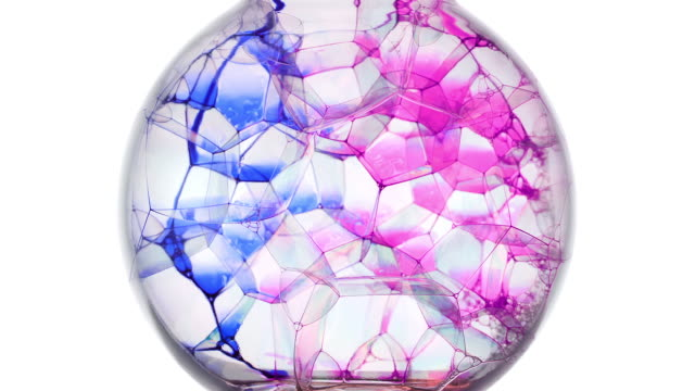 stockvideo's en b-roll-footage met slow motion and close up, blue and pink ink spreading out on soap bubbles in a sphere - versmelten