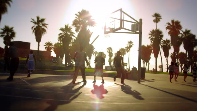 Slow motion and lens flare shot of a basketball game near Venice Beach, California