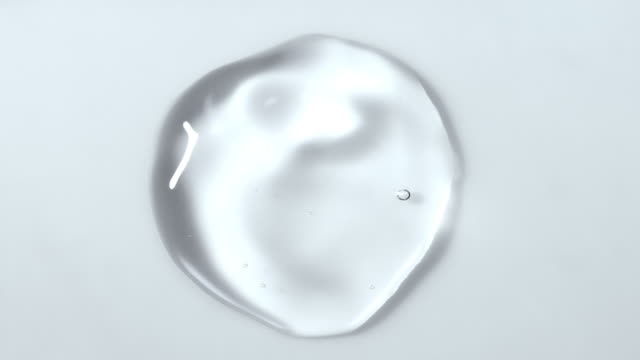 slow motion and super macro shot of a crystal clear water droplet bouncing and moving around on a white surface - sphere stock videos & royalty-free footage