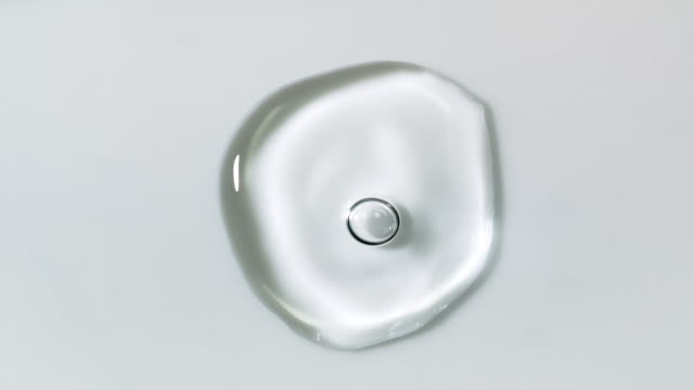 slow motion and super macro shot of a crystal clear water droplet bouncing and moving around on a white surface - single object stock videos & royalty-free footage