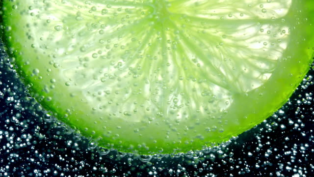 slow motion and super macro shot of soda bubbles flowing up over a back lit half slice of lime behind against a black background - lime stock videos & royalty-free footage