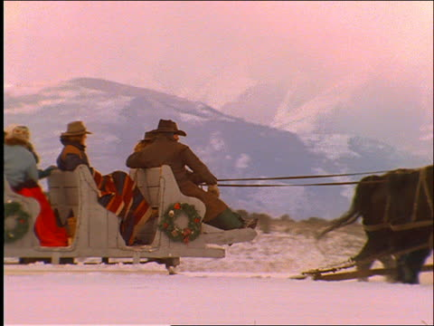 slow motion PAN and zoom out of people riding horse-drawn sleigh / Mtns in background